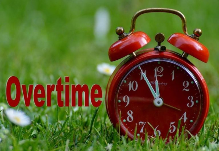 a red clock in a field of grass representing overtime